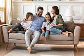 Happy parents with son and daughter relaxing on couch