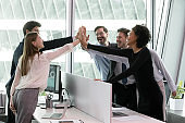 Overjoyed diverse employees giving high five, celebrating successful project finish.