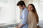 Loving young newlyweds cuddle cooking at home together