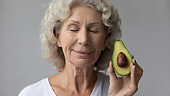 Head shot satisfied mature woman with closed eyes holding avocado