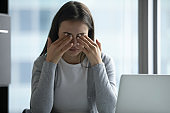 Exhausted female employee suffer from headache at workplace