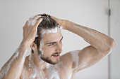 Young man washing taking shower in bathroom