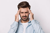 Unwell caucasian man massage temples suffering from severe headache