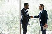 Happy diverse businessmen handshake closing deal after negotiations