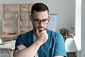 Thoughtful young businessman wearing glasses thinking about problem solution