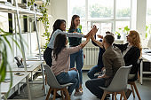 Excited diverse colleagues give high five motivated for shared success