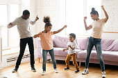 African family with children dancing in modern living room
