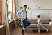 Happy young dad and son dancing in living room