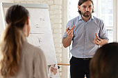 Motivated male speaker make whiteboard presentation for colleagues