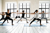 Group of people practicing yoga asanas doing Warrior Two exercise