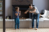 Young father and little son dancing at home