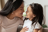 Caring young asian mother enjoying communicating with cute small child.