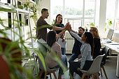 Excited multiracial coworkers give high five celebrating success in office