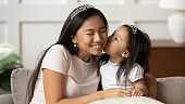 Little funny vietnamese ethnicity kid girl kissing mommy.