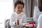 African American dad give wrapped present to little son
