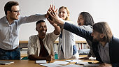 Excited diverse business team giving high five at meeting