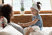 Daughter holds stethoscope imagines herself doctor listen mother heartbeat