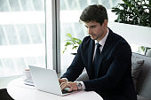 Young business man typing on computer sitting on sofa