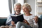 Smiling mature man and woman enjoying literature together