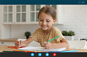 Smiling little girl talk on video call drawing