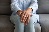 Close up of old woman sit with hands folded