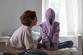 Stubborn teenage girl putting hood on avoiding talk with mom