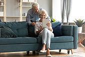 Happy mature grey-haired woman shopping online with husband.