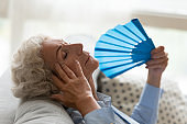 Senior woman suffer from hot weather using hand fan