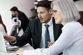 Experienced business man and woman discussing startup ideas using computer