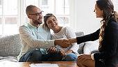 Smiling multiethnic couple handshake realtor greeting at meeting