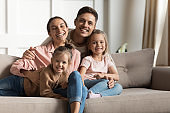 Smiling parents hug small kids daughters relaxing on couch, portrait