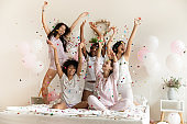 Happy multiethnic girls catching playing with falling multi colored confetti