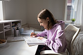 Teen girl studying alone reading textbook sitting at home desk