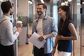 Multiethnic colleagues met in office hallway having informal positive conversation