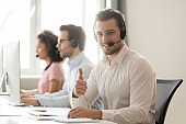 Smiling customer support service operator in headset showing thumbs up