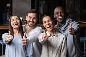 Portrait of happy young people show thumbs up recommending service