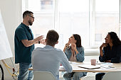 Diverse employees listening to confident coach mentor at meeting