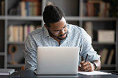 Focused african business man make notes study work on laptop