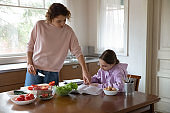 Mom helping teenage daughter with studies cooking at kitchen table