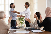 Smiling businessman shake hand of male newcomer at meeting