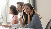 Smiling woman call center operator in headset showing thumbs up