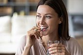 Close up smiling woman taking pill, holding water glass