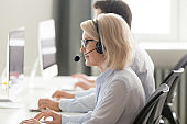 Mature call center operator in headset consulting client online