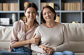 Portrait of adult daughter and middle aged mother at home