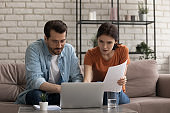 Focused young married couple looking at computer screen, planning budget.