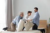 Three generations of men play with pillows on bed indoors