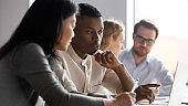 Multiracial coworkers brainstorm discuss business ideas at meeting
