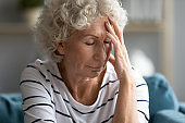 Unhealthy old mature hoary grandmother suffering from migraine.