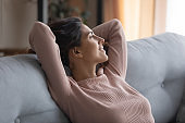 Smiling young woman relax on sofa look in distance dreaming