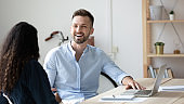 Laughing businessman talking with businesswoman using laptop in boardroom.